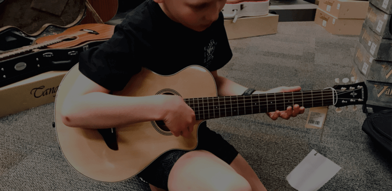 Child with 3/4 size guitar