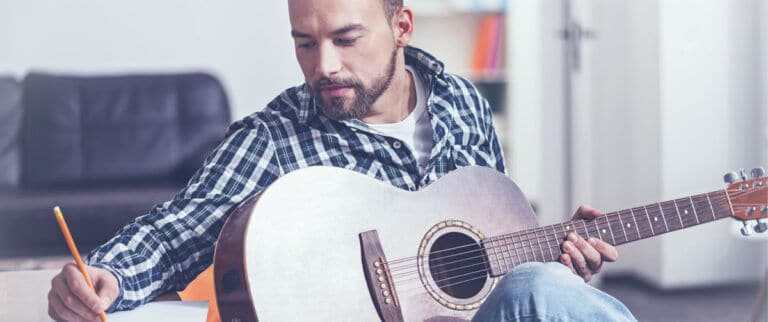 Man writing music on acoustic guitar
