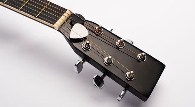 Guitar picks on acoustic guitar headstock